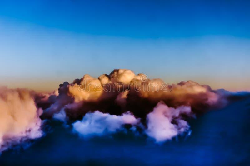 Vista bonita da janela do avião - nuvens brancas azuis róseos imagem de stock