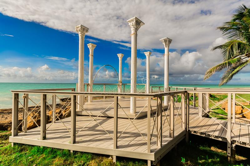 Vista bonita das colunas velhas do miradouro do casamento que estão na plataforma de madeira à moda perto da praia e do oceano tr foto de stock royalty free