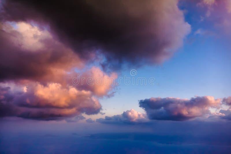 Vista bonita das nuvens brancas, roxas e róseos da janela do avião - foto de stock royalty free