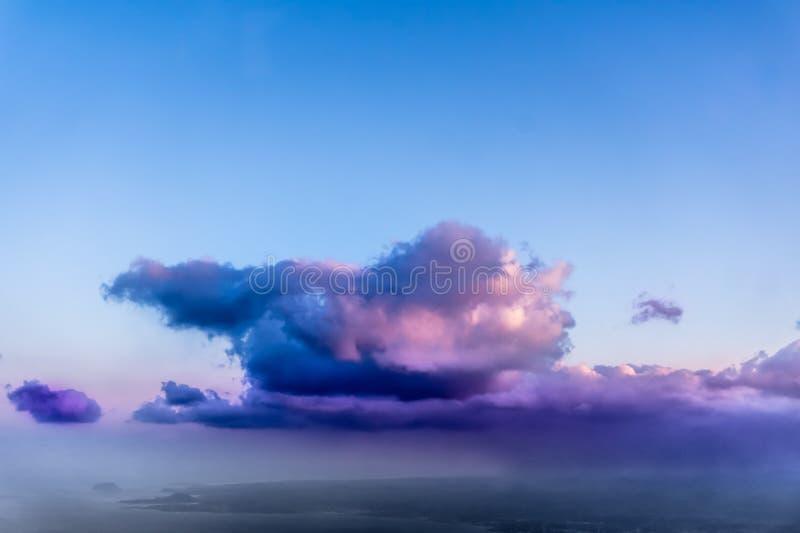 Vista bonita das nuvens brancas, roxas e róseos da janela do avião - imagem de stock royalty free