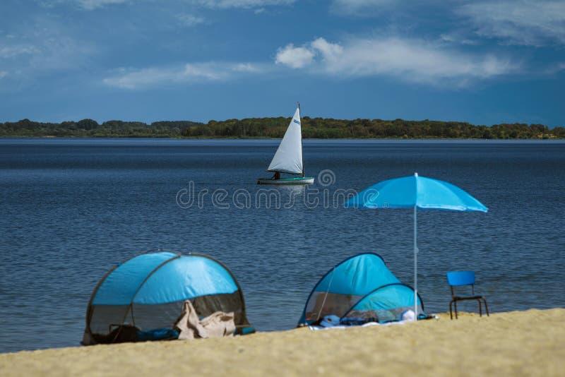 Vista bonita das opções do recurso, dos esportes barco e das barracas com os guarda-sóis na praia imagem de stock royalty free