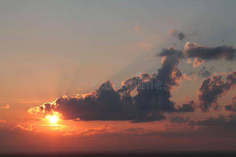 Vista bonita de um sol vermelho ajustado com nuvens fotografia de stock