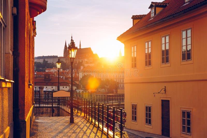 Vista bonita do castelo de Praga no por do sol de uma rua hist?rica com as l?mpadas de g?s sobre o rio Vltava Praga, Czechia famo fotografia de stock royalty free