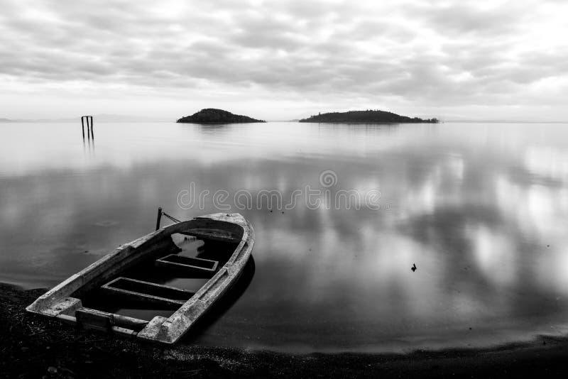 A vista bonita do lago Úmbria Trasimeno no crepúsculo, com um barco pequeno, velho encheu-se parcialmente pela água, perfeitament fotografia de stock