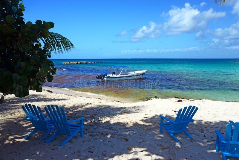Vista bonita do mar das caraíbas, do mar azul, de uma ponte quebrada e de um barco de um Sandy Beach com as cadeiras azuis na ilh imagens de stock royalty free