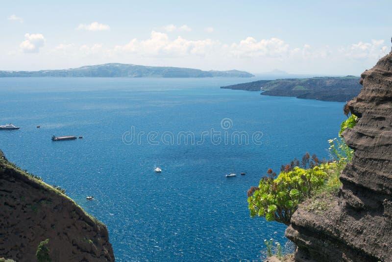 Vista bonita do mar, dos iate e das montanhas cobertos com as flores Ilha grega de Santorini em um dia ensolarado morno Curso ao fotos de stock