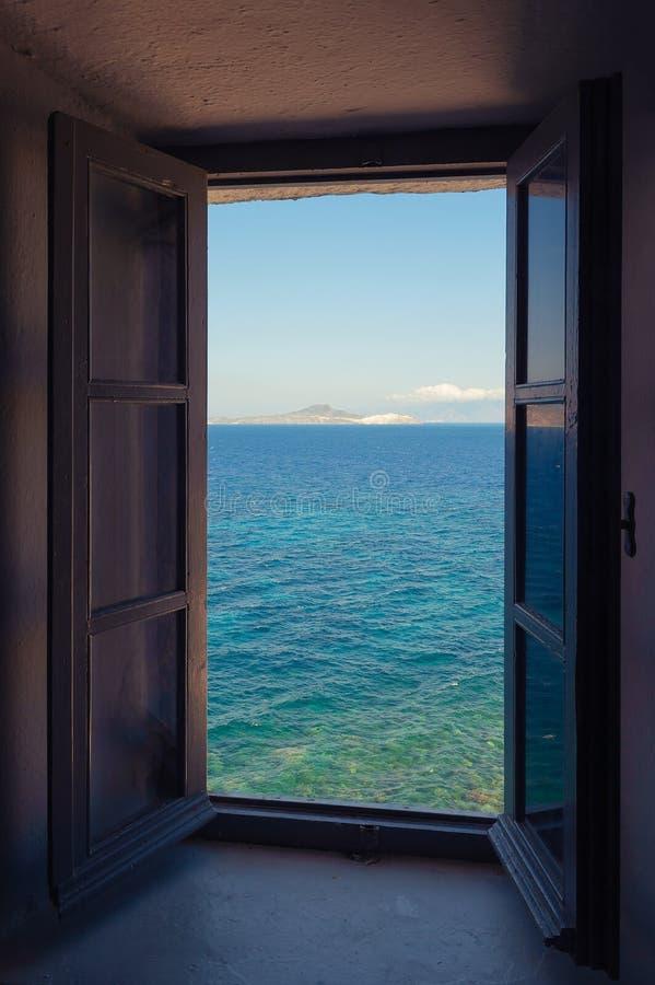 Vista bonita do mar e da ilha coloridos turquesa de uma janela velha em Grécia foto de stock