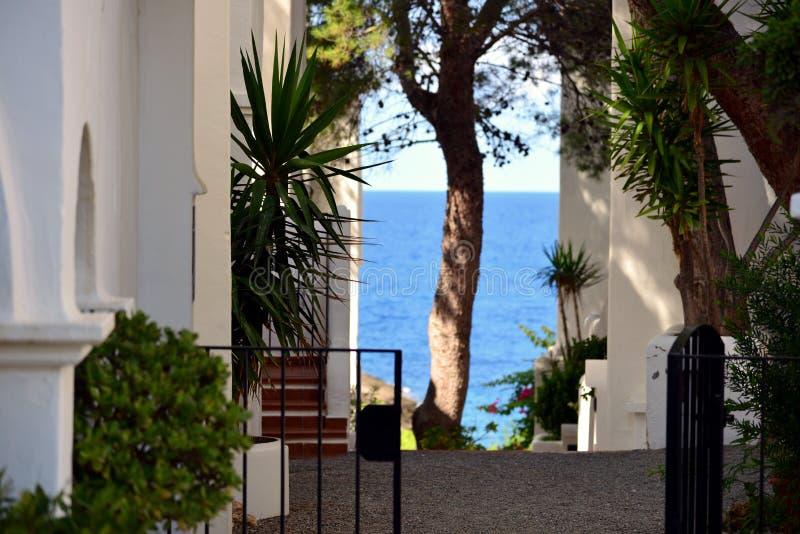 Vista bonita do mar Mediterrâneo colorido através de uma jarda em Ibiza imagem de stock