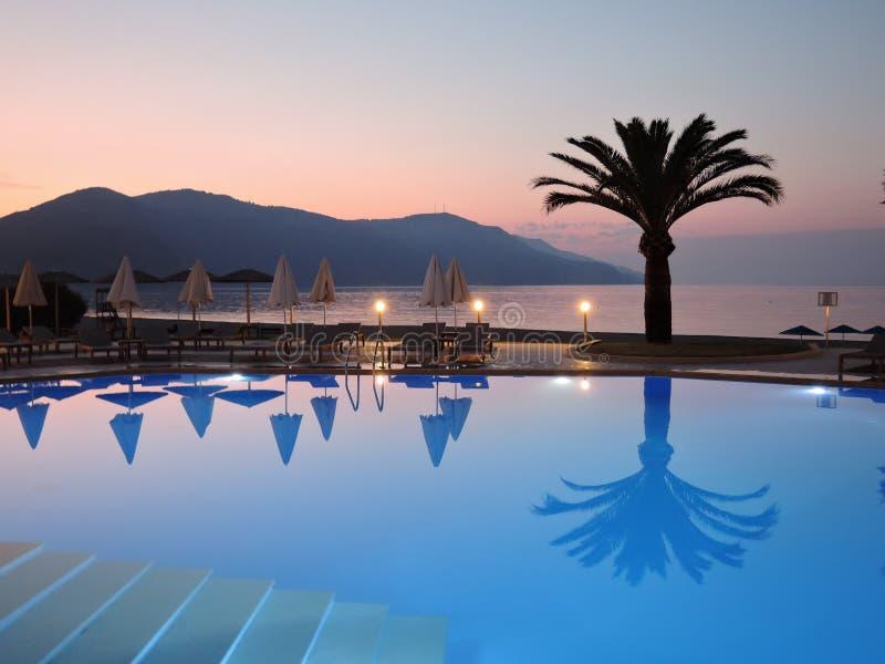 A vista bonita do terraço do hotel à associação, palmeiras dobrou barracas da praia, montanha na distância e por do sol sobre fotos de stock
