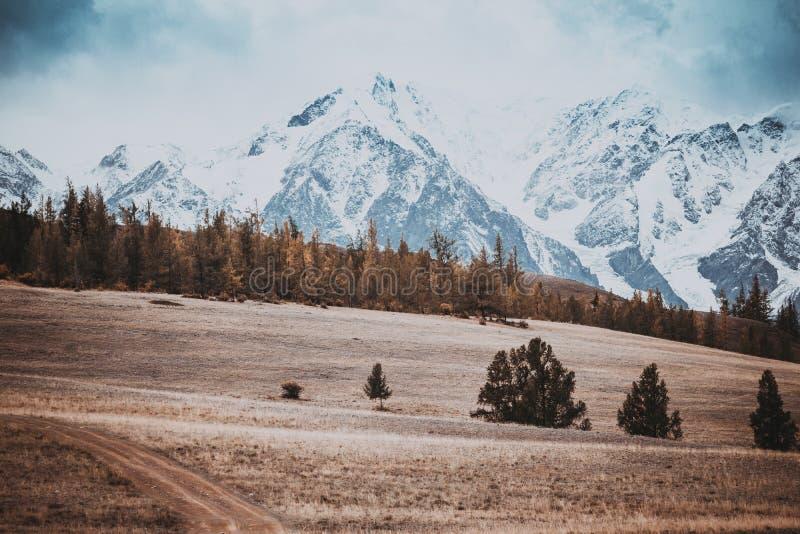 Vista bonita dos montes com uma estrada de terra aos picos nevado imagens de stock