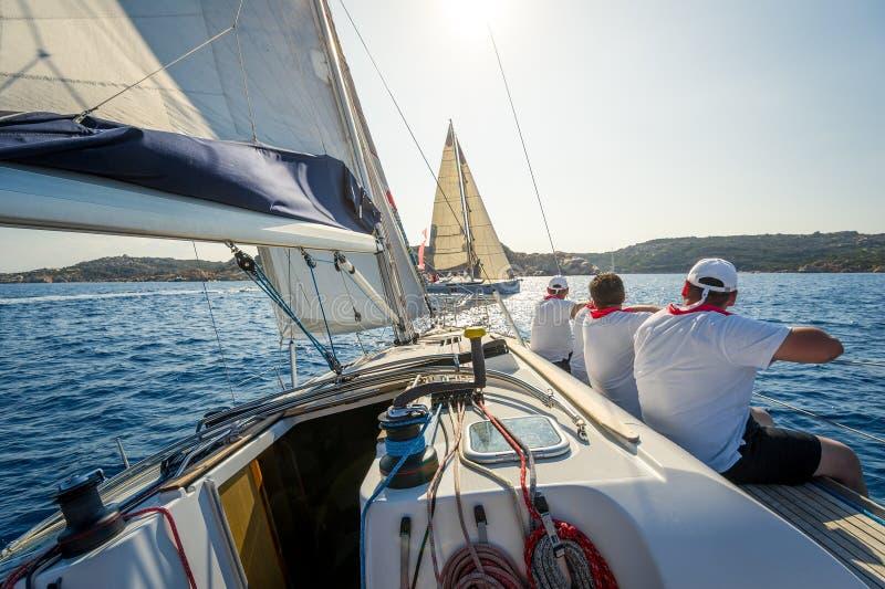Vista a bordo di corsa dell'yacht di navigazione con una squadra che si siede dal lato di dritta fotografie stock