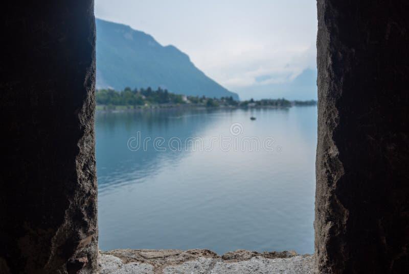 Vista borrada bonita do lago geneva no fundo do céu nebuloso e da montanha que olha da janela de pedra em castelo de chillon, o m fotografia de stock