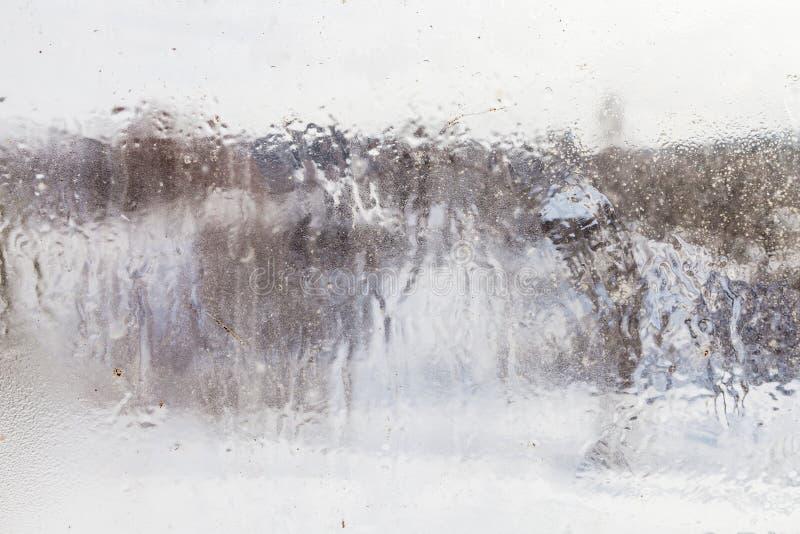 vista borrosa del pueblo a través de la ventana congelada foto de archivo libre de regalías