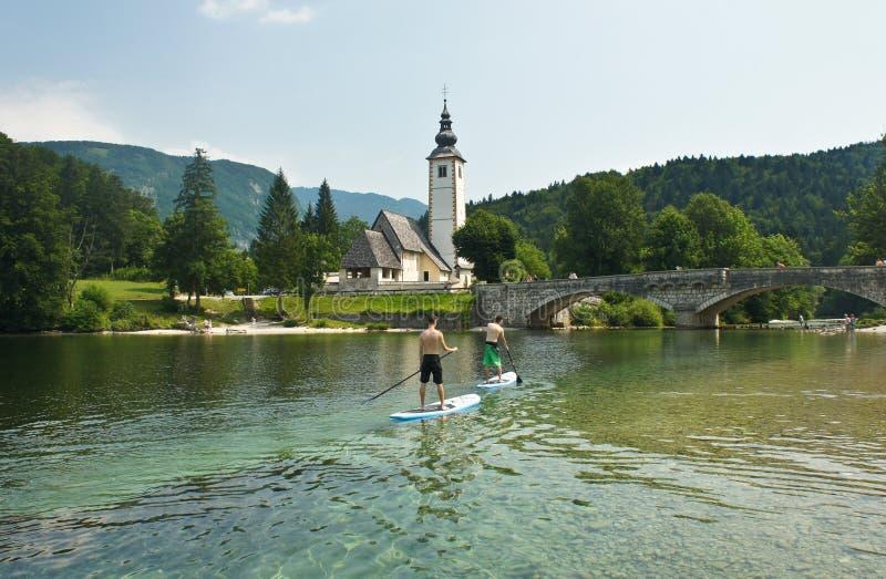 Vista cênico da igreja de St John o batista, ponte, montanhas de Julian Alps e lago, Bohinj, Eslovênia imagem de stock