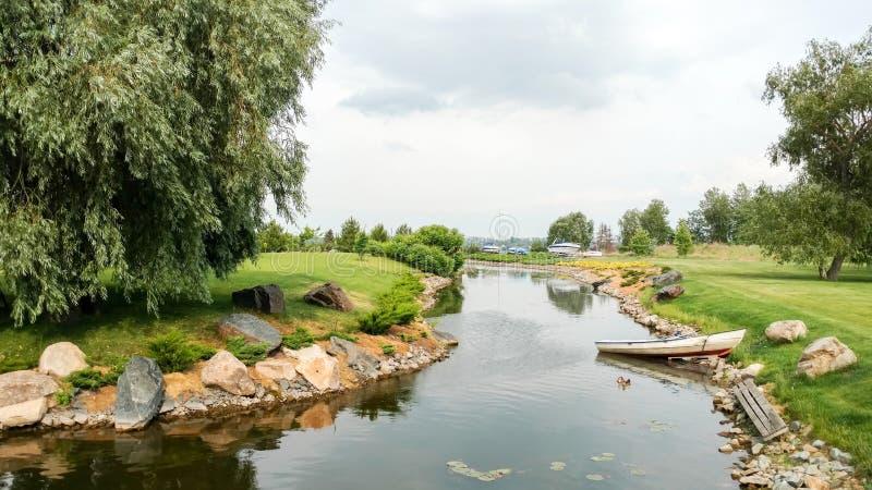 Vista cênico de um rio pequeno com costa rochosa, lírios de água, uma ilha com um salgueiro, um gramado ordenadamente aparado, pa imagem de stock
