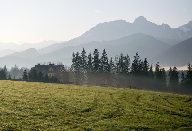 Vista cênico de um vale maravilhoso com construção de casa rural da exploração agrícola com as montanhas no fundo na manhã ensola imagens de stock