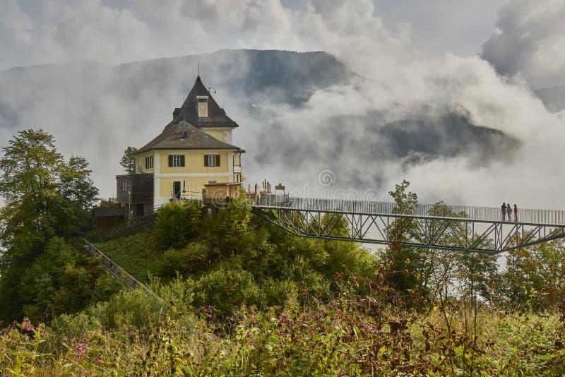 Vista cênico de uma construção do restaurante acima do skywalk perto da vila de Halstatt em Áustria fotografia de stock
