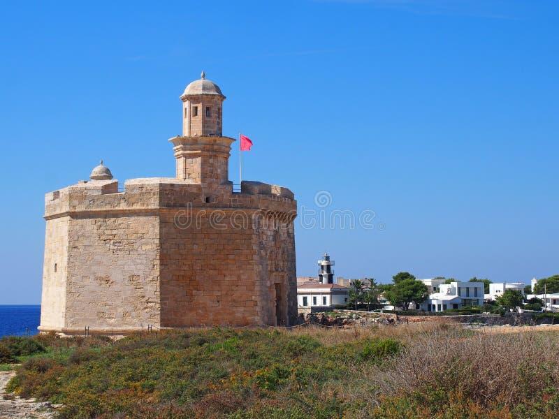 Vista cênico do castelo histórico no menorca do ciutadella com farol e de construções nos penhascos com o mar e a SU azuis brilha imagem de stock