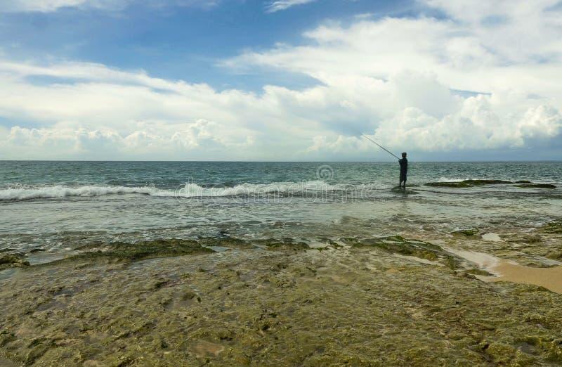 Vista cênico do litoral rochoso com a silhueta do homem na pesca do horizonte com a haste relaxada em praia tropical bonita surpr imagem de stock royalty free