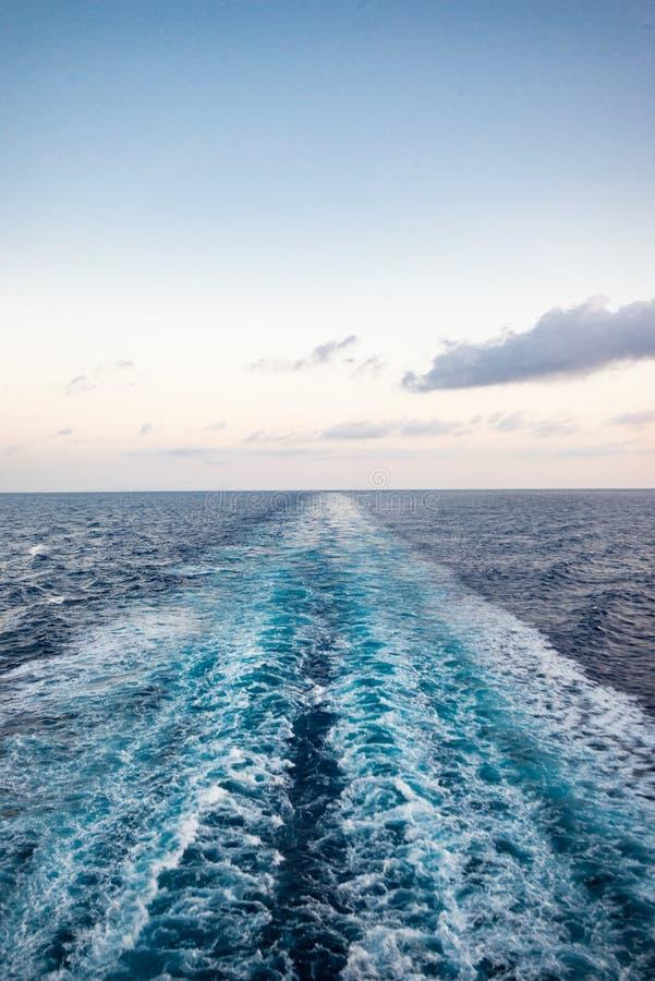 Vista cênico do mar da proa de um navio de cruzeiros luxuoso, contra o nascer do sol em um céu azul bonito foto de stock royalty free