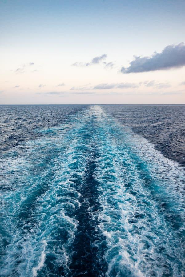 Vista cênico do mar da proa de um navio de cruzeiros luxuoso, contra o nascer do sol em um céu azul bonito imagem de stock