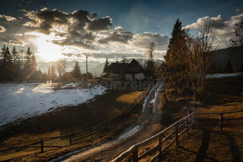 Vista cênico em montanhas alpinas da floresta com a casa de madeira isolada do chalé no ambiente ensolarado idílico do inverno, p imagem de stock royalty free