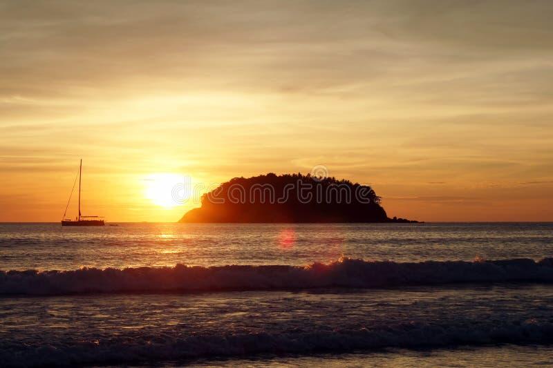A vista cênico em um mar com um bote e na ilha durante um por do sol imagens de stock royalty free