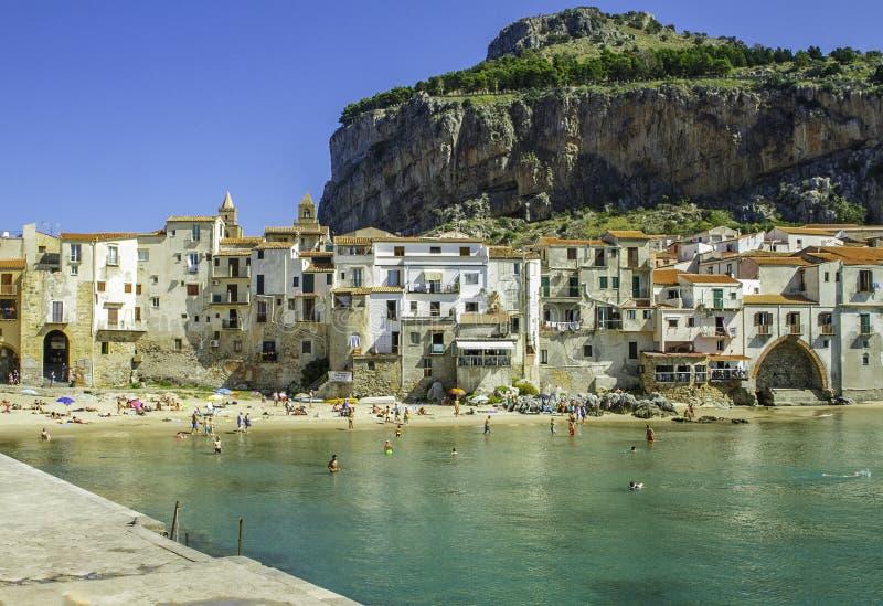 Vista cênico espetacular das casas brancas portuárias, características de Cefalu ', da água clara e da praia em Sicília imagens de stock