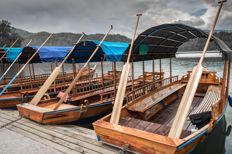 A vista cênico no pletna liso de madeira bonito dos barcos de enfileiramento no lago sangrado, slovenia, vai conceito verde fotografia de stock