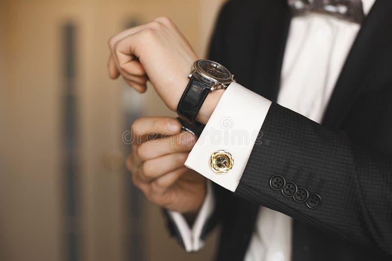 Vista cercana de los relojes de lujo en la mano de un hombre de negocios hermoso en un smoking y en una camisa con las mancuernas fotografía de archivo