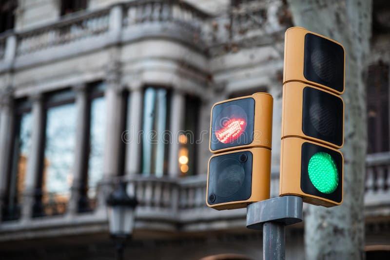 Vista cercana de un tráfico rojo quebrado verde del semáforo y del peatón rojo claro con el fondo borroso imagenes de archivo