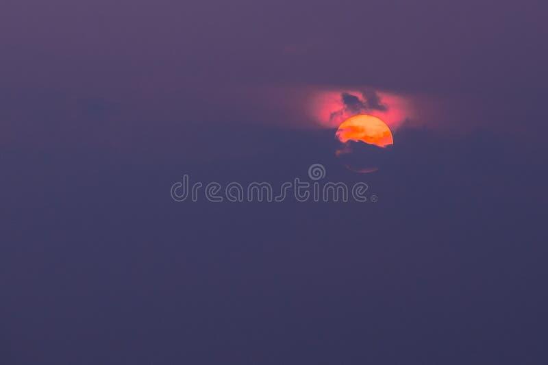 Vista cercana del disco anaranjado de Sun cubierto en parte por las nubes con resplandor carmesí encima de, Violet Sky Background imágenes de archivo libres de regalías