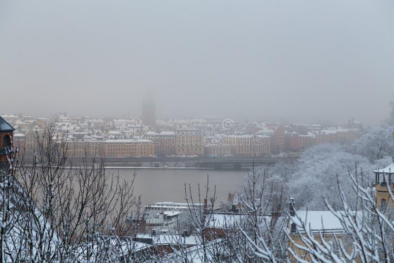 Vista clássica da Suécia de Éstocolmo e da cidade velha atrás da ponte em um dia de inverno nevoento fotos de stock royalty free