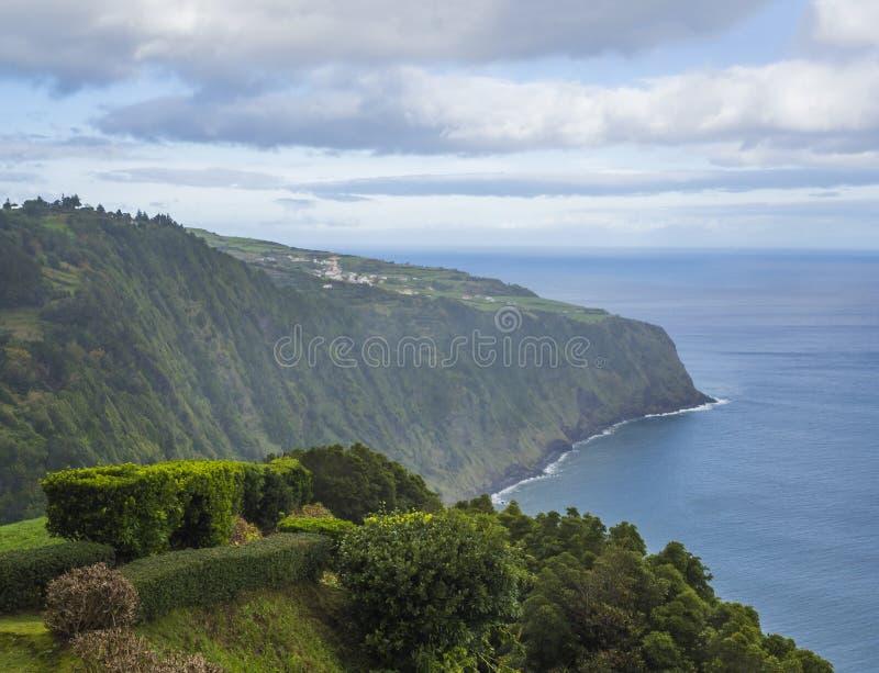 A vista com penhascos íngremes, o mar, o arbusto da conversão e o jardim do ponto de vista Miradouro a Dinamarca Ponta fazem Soss fotografia de stock