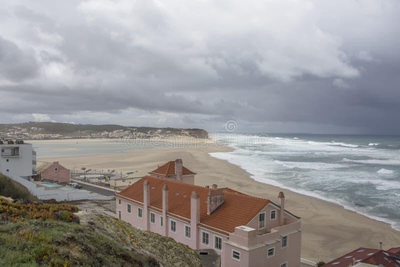 Vista completa sulla spiaggia di Foz do Arelho con palazzi e persone che giocano a Kite Surf sulla laguna di Obidos immagine stock