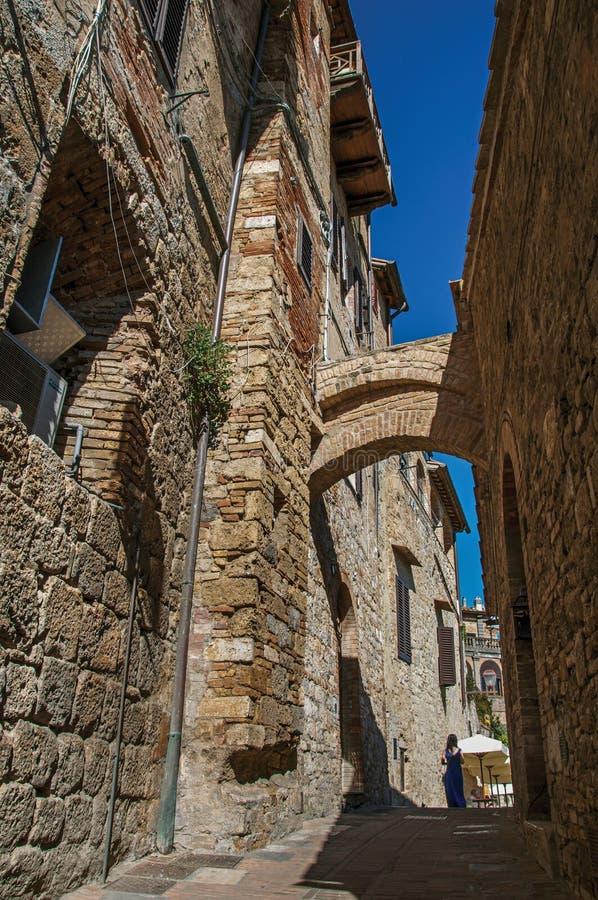 Vista da aleia estreita com as construções, o arco velho e a mulher andando em San Gimignano imagens de stock
