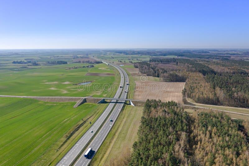 Vista da altura na estrada com carros, esticando afastado entre os campos e as florestas fotos de stock