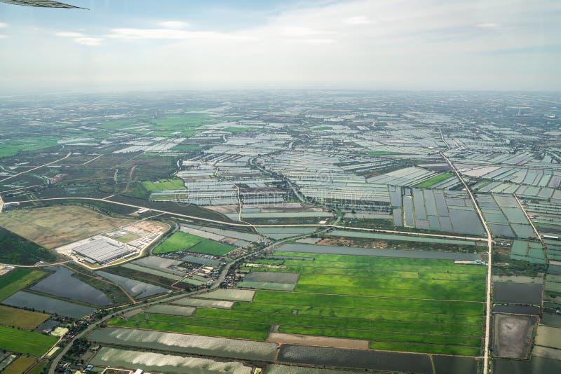 A vista da baixa verde do campo e da exploração agrícola e da cidade no meio de Tailândia Disparou de Jetplane fotos de stock royalty free