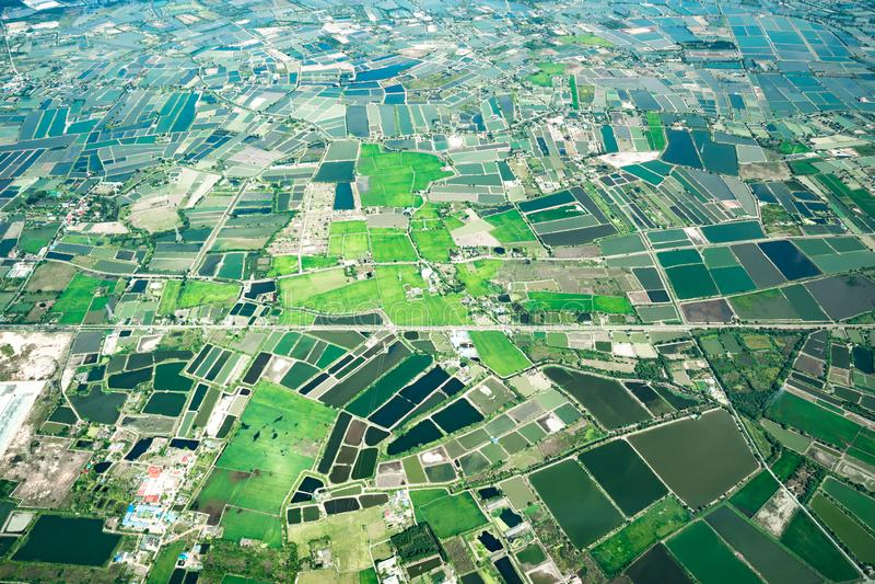 A vista da baixa verde do campo e da exploração agrícola e da cidade no meio de Tailândia Disparou de Jetplane fotografia de stock royalty free