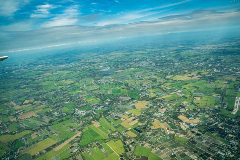 A vista da baixa verde do campo e da exploração agrícola e da cidade no meio de Tailândia Disparou de Jetplane foto de stock royalty free