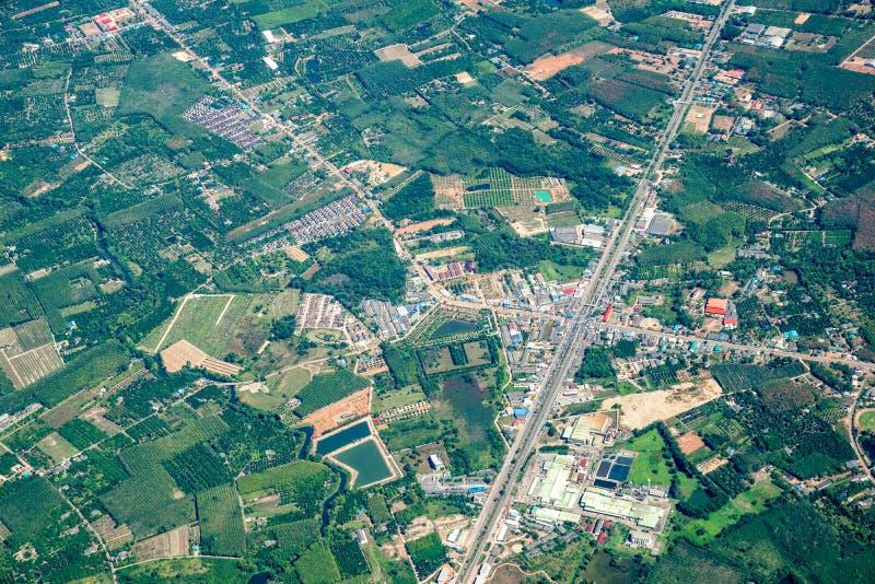 A vista da baixa verde do campo e da exploração agrícola e da cidade no meio de Tailândia Disparou de Jetplane fotos de stock