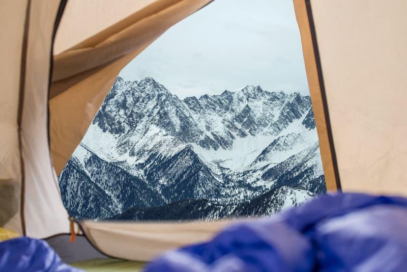 Vista da barraca em montanhas neve-tampadas Viagens e expedições no selvagem Conceito do acampamento fotografia de stock royalty free