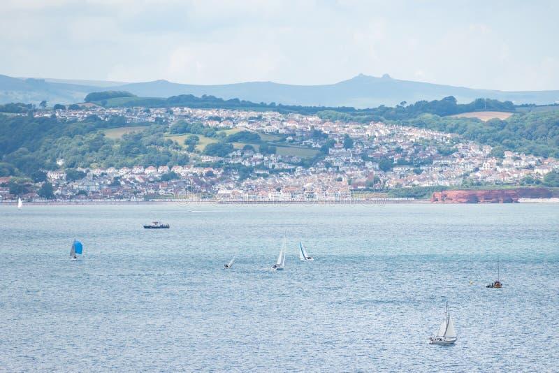 Vista da Berry Head delle barche a vela davanti a Preston Sands ed a Marine Parade sul lungonmare fra Paignton e Torquay immagine stock libera da diritti