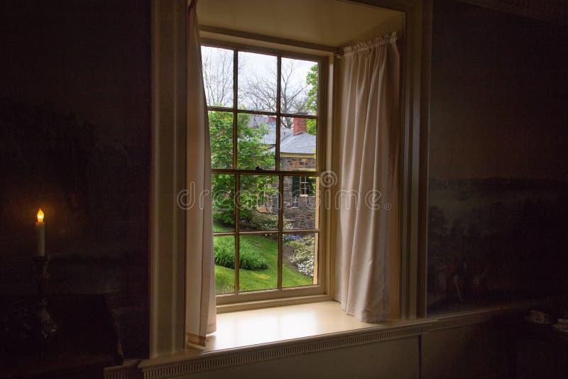 Vista da casa do tijolo através da janela velha imagem de stock