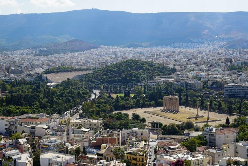 Vista da cidade de Atenas da acrópole que mostra a ruína antiga, a arquitetura das construções, ruas urbanas, árvores verdes e fu imagem de stock royalty free