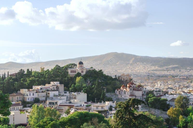 Vista da cidade de Atenas, da igreja e das montanhas da acrópole Árvores verdes e céu azul fotografia de stock royalty free