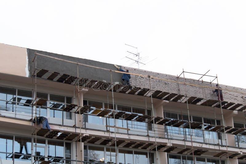 Vista da construção com andaime Os trabalhadores reparam a fachada imagem de stock royalty free