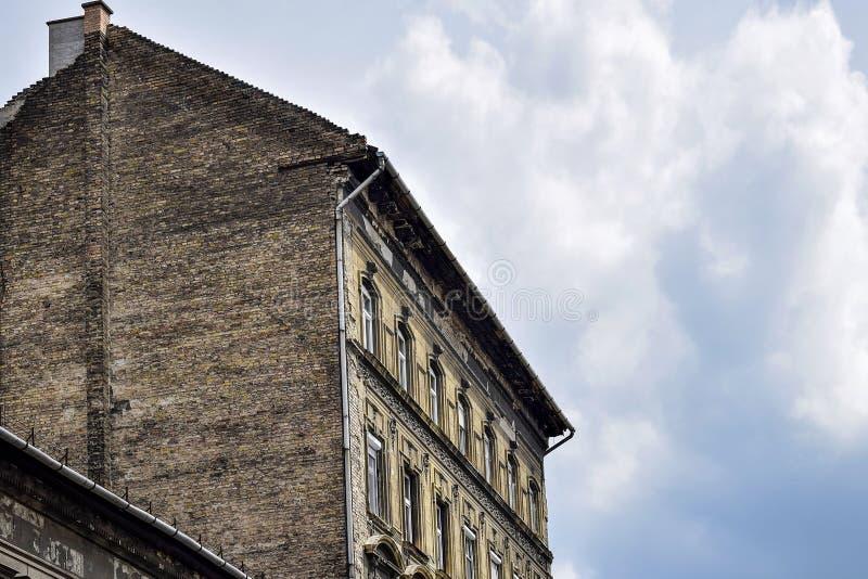 Vista da construção de tijolo velha do arranha-céus no fundo do céu nebuloso imagem de stock