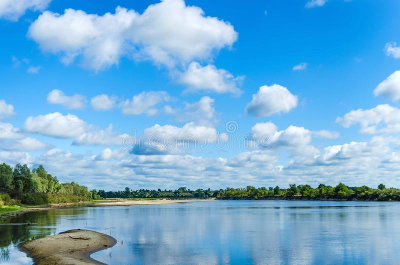 A vista da costa ao rio derramado largo com áreas rasas imagem de stock