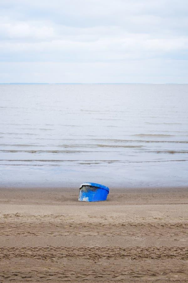 Vista da cubeta na praia com o céu e do rio no fundo imagens de stock
